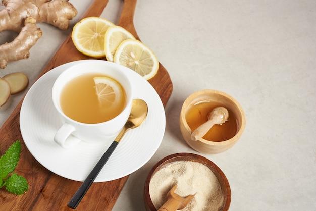Ingredienti del tè allo zenzero, tè salutare, confortante e riscaldante con una ricetta semplice. tè allo zenzero e ingredienti - limone, miele vista dall'alto. lay piatto. appena dal giardino biologico di crescita domestica. concetto di cibo.
