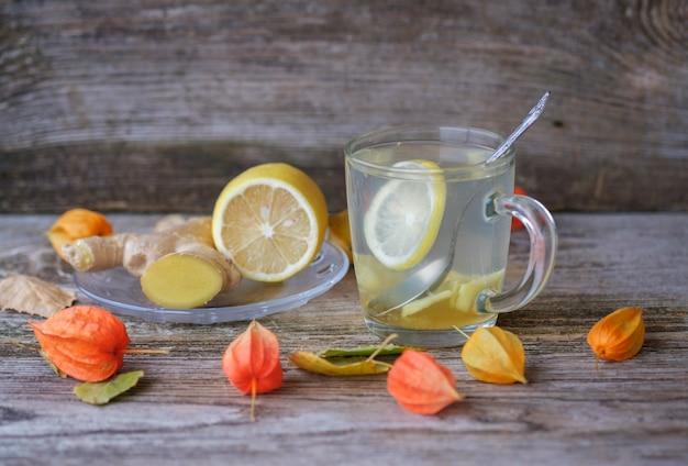 Tè allo zenzero con limone e miele in un bicchiere di vetro su una tavola di legno