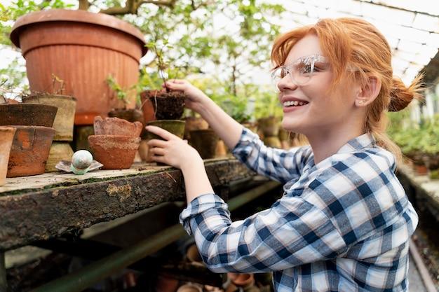 Ginger donna che si prende cura delle sue piante in una serra