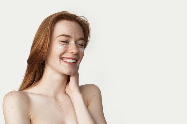 La donna allo zenzero con le lentiggini sta applicando la crema sul viso sorridente su un muro bianco con le spalle nude