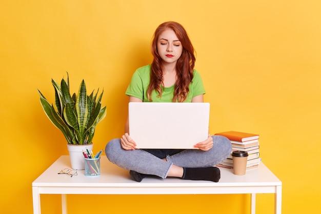 Ginger giovane studentessa seduta sul tavolo, utilizzando il computer portatile durante lo studio, guardando lo schermo del dispositivo con espressione facciale seria concentrata, la ragazza si siede vicino a vaso di fiori, pila di libri, penne, tazza.