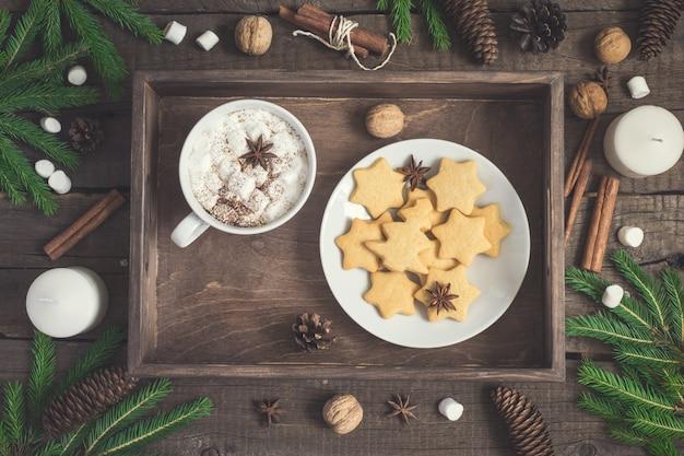 Biscotto di panpepato sotto forma di stelle e tazza di cacao sul vassoio rustico. sfondo di cibo di natale.
