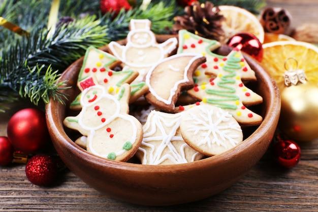 Biscotti di panpepato in ciotola con decorazioni natalizie su sfondo di tavolo in legno