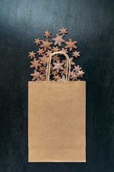 Biscotti di panpepato a forma di stelle e borsa artigianale su superficie nera