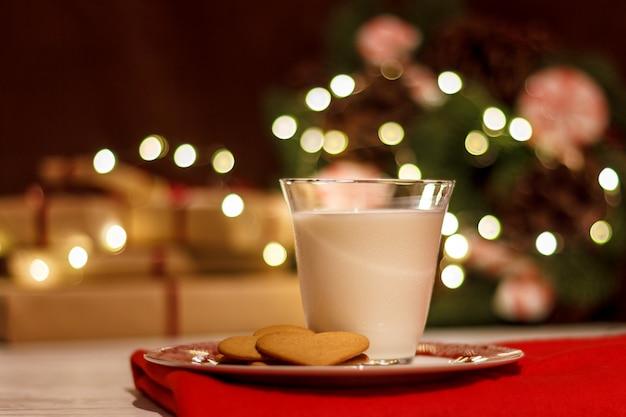 Biscotti al pan di zenzero e un bicchiere di latte per babbo natale sullo sfondo di una ghirlanda di natale e una corona di aghi di pino