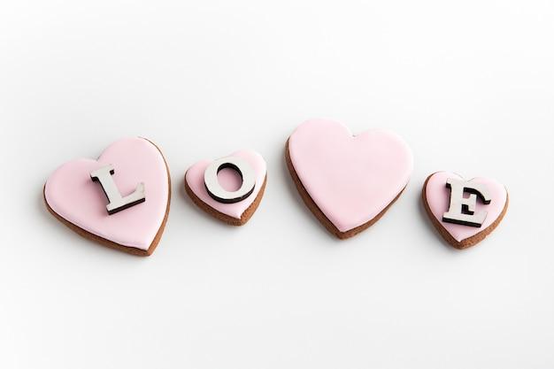 Gingerbread cookies a forma di cuore con glassa di zucchero rosa su fondo bianco e scritta amore.