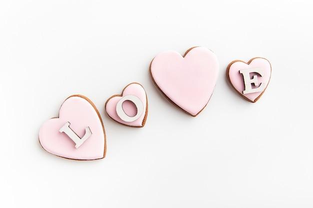 Biscotti di panpepato a forma di cuore con glassa di zucchero bianco su fondo bianco e scritta amore.