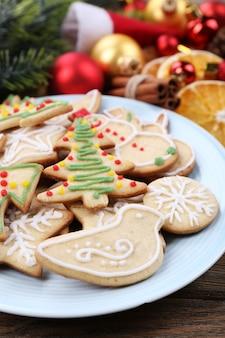 Biscotti di panpepato su piatto con decorazioni natalizie su tavola di legno