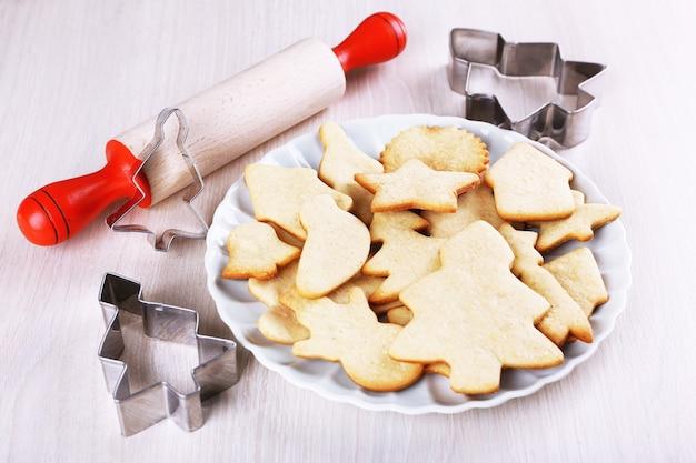 Biscotti di panpepato su piastra con tagliabiscotti in rame e mattarello su tavola di legno
