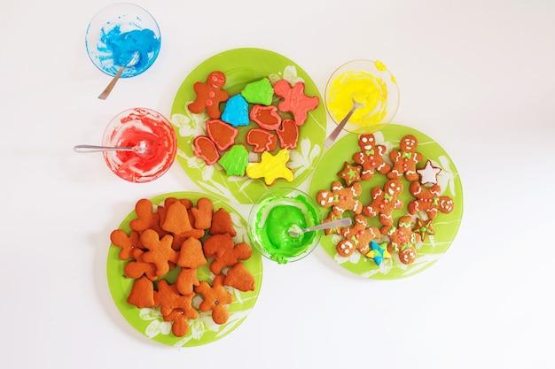 Biscotti di panpepato su piatti e mastice multicolore per panpepato sul tavolo bianco. cottura di natale. preparazione per le vacanze, natale, capodanno.