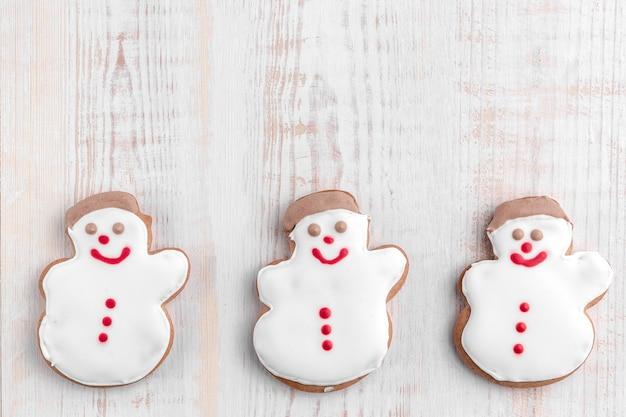 Pupazzo di neve a forma di biscotti di panpepato su un fondo di legno strutturato luminoso