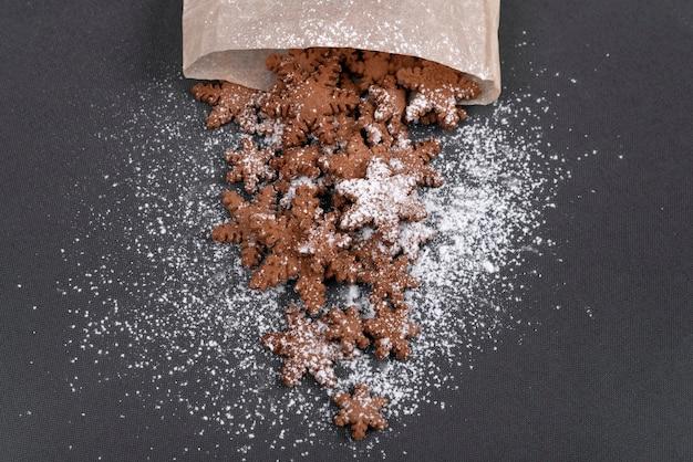 Biscotti di panpepato a forma di fiocchi di neve cosparsi di zucchero a velo. vista dall'alto, sfondo grigio.