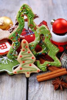 Biscotti di panpepato con decorazioni natalizie sullo sfondo della tavola in legno