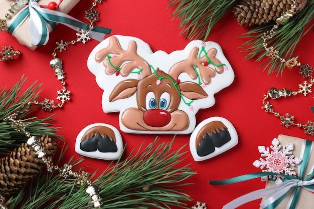 Gingerbread deer su sfondo rosso, regali di natale
