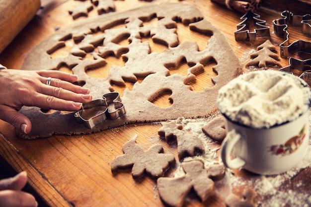 Pasta di pan di zenzero e mani di donna che preparano torte di biscotti di natale.