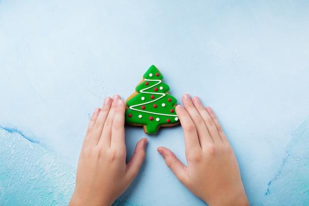 Pan di zenzero sotto forma di alberi di natale su un blu, una tazza di cioccolata calda e caramelle nelle mani dei bambini.