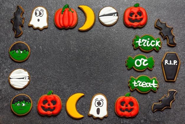 Lo spazio della copia di halloween del pan di zenzero ha centrato il pan di zenzero luminoso su uno zombi fantasma della zucca dello sfondo di pietra scura