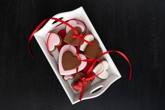 Vista dall'alto di biscotti cuore di panpepato su sfondo nero. festa della mamma. giornata della donna. san valentino.