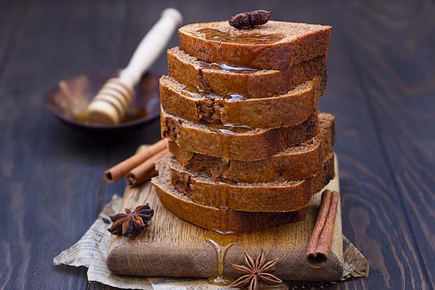 Pan di zenzero e pagnotta di miele agglutinare con cannella e anice su fondo di legno. stile rustico.