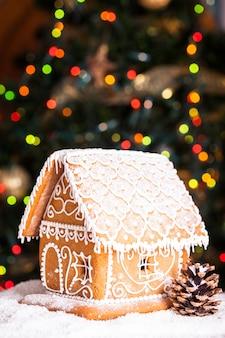 Casa di pan di zenzero su luci sfocate di abete decorato di chrismtas