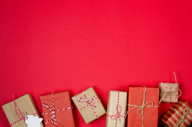 Casa di pan di zenzero molti regali in carta da regalo kraft bokeh su biglietto di auguri vacanze rosso