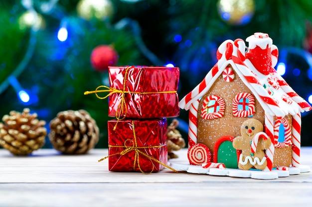 Casa di marzapane su un tavolo di legno insieme a regali di natale su un albero di natale.