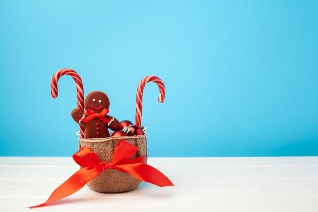 Gingerbread man e bastoncini di zucchero in un cesto su sfondo blu
