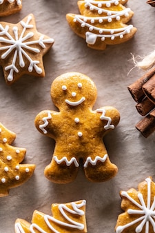 Omino di pan di zenzero e altri biscotti natalizi insieme alla cannella.