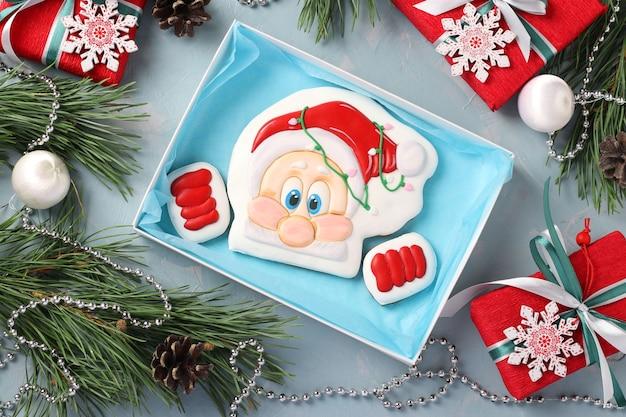 Gingerbread santa in scatola su sfondo azzurro, regali di natale o festa di noel. vista dall'alto