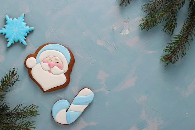 Pan di zenzero babbo natale, canna e fiocco di neve su uno sfondo azzurro, orientamento orizzontale, spazio di copia