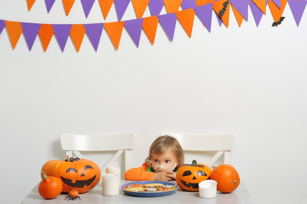 Il costume da zucca girin non festeggia halloween e indossa una maschera facciale che protegge da covid19