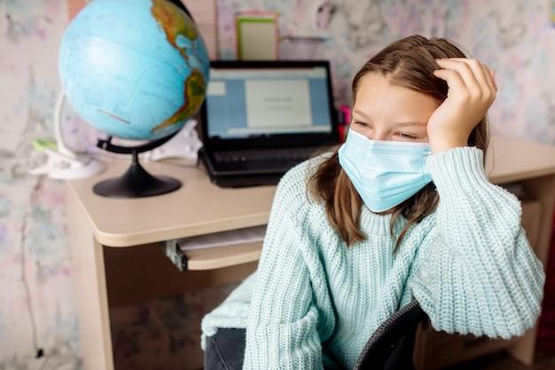 Ragazza di 10 anni in una maschera sull'apprendimento a distanza a casa. il bambino è annoiato, è stanco