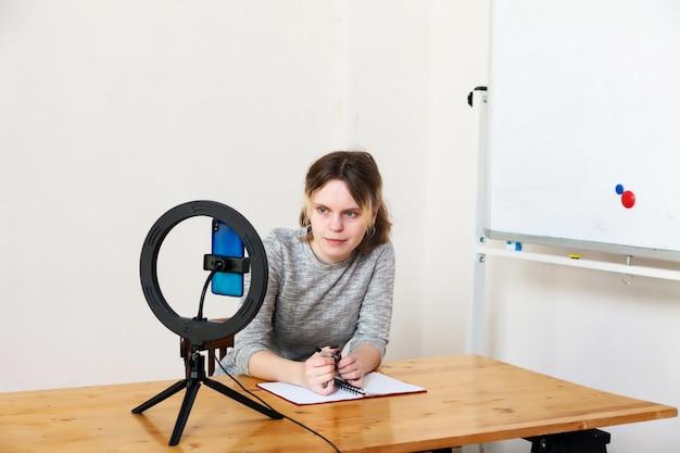Ragazza di 16 anni che registra video su smartphone e si illumina con lampada ad anello al tavolo nella stanza luminosa