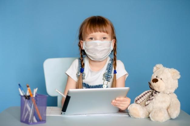 Una ragazza di 5-6 anni seduta a un tavolo svolge compiti remoti a casa sul tablet. isolare su una parete blu. coronavirus, bambino mascherato.