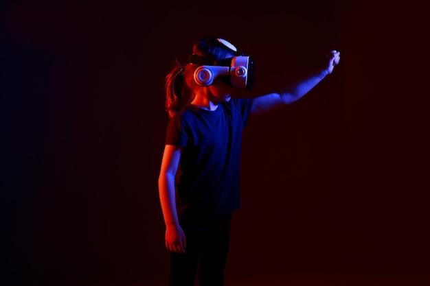 Ragazza di 5 anni sperimentando il gioco dell'auricolare vr su una superficie colorata. bambino che utilizza un gadget di gioco per la realtà virtuale. occhiali futuristici in giovane età. tecnologia virtuale.