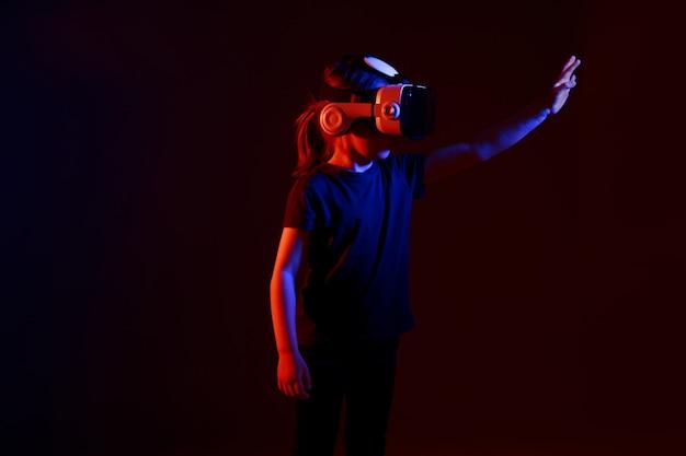 Ragazza di 5 anni sperimentando il gioco dell'auricolare vr su una superficie colorata. bambino che utilizza un gadget di gioco per la realtà virtuale. occhiali futuristici in giovane età. tecnologia virtuale. Foto Premium