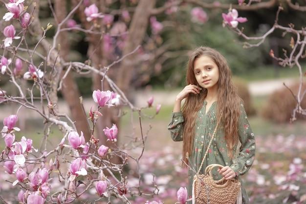 Ragazza 8-9 anni nel giardino con alberi di magnolia