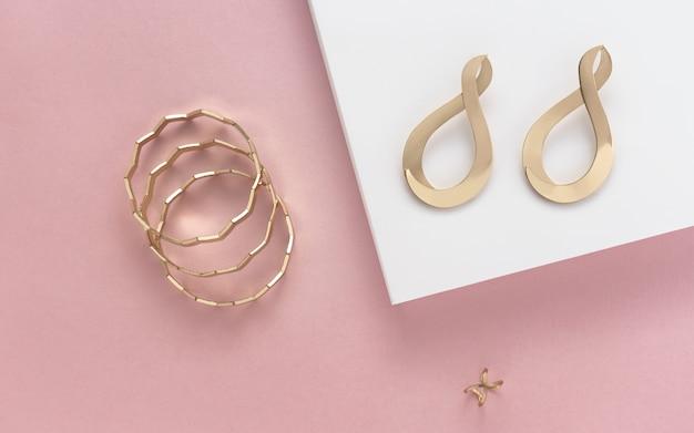 Orecchini e braccialetti dorati degli accessori della ragazza sulla parete di colore pastello con lo spazio della copia