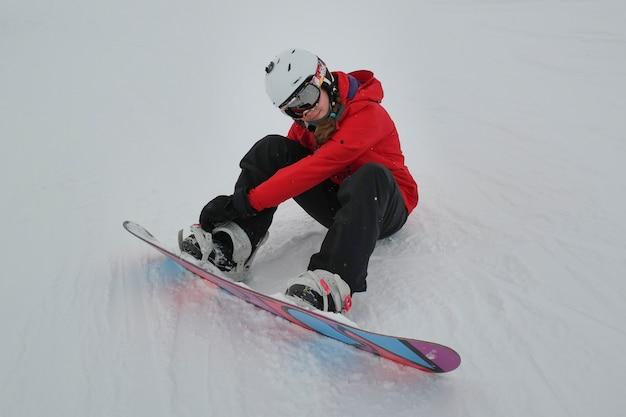 Ragazza che regola snowboard, whistler blackcomb, vancouver, columbia britannica, canada