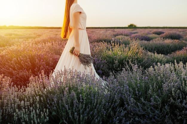 La ragazza ammira il tramonto nei campi di lavanda.
