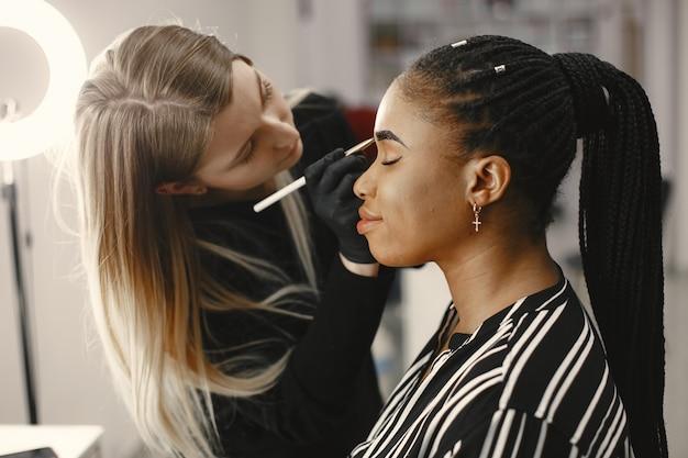Ragazza africana. donna che fa le sopracciglia. ragazze in un salone di bellezza. Foto Premium