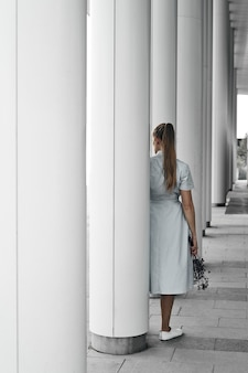 Una ragazza sullo sfondo di colonne bianche rotonde tiene un ramo tra le mani. geometria negli edifici, passeggiate in città. copia spazio.