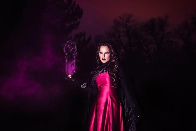 La ragazza sola di notte nella foresta prepara una pozione e meraviglie per il matrimonio, circondata da candele e fumo