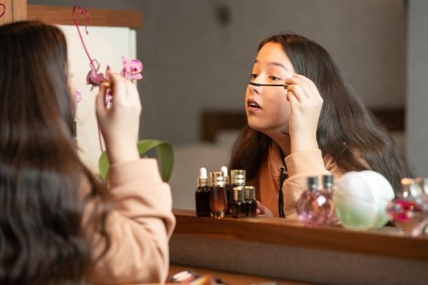 La ragazza applica il trucco seduto davanti allo specchio.