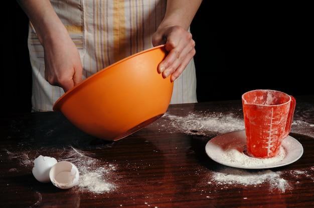 Una ragazza con un grembiule in una cucina scura impasta la pasta in una tazza d'arancia.