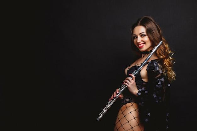 Una ragazza artista in costume con un flauto su sfondo nero. flauto in mano. ã â¡oncept di un poster musicale. foto per la copertina di una rivista, sito web con spazio per un'iscrizione o un logo