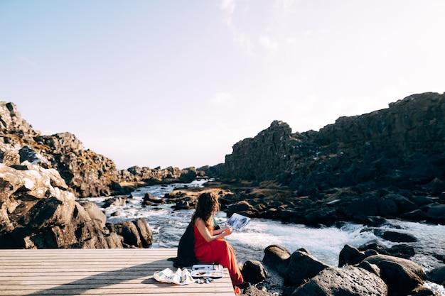 L'artista ragazza dipinge un'immagine nell'album con acquerelli vicino alla cascata ehsaraurfoss ehsarau