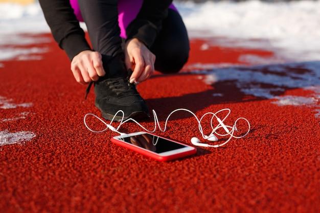 Ragazza atleta in scarpe da ginnastica nere, accovacciato sulla pista rossa per correre. vicino c'è un telefono con le cuffie cablate. freddo tempo nevoso