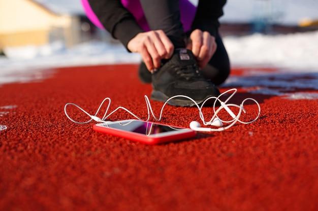 Ragazza atleta in scarpe da ginnastica nere, accovacciato sulla pista rossa per correre.