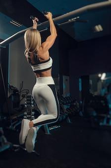 L'atleta ragazza in abbigliamento sportivo si sta allenando in palestra